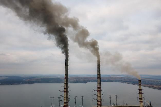 Vue aérienne des tuyaux hauts de la centrale au charbon avec de la fumée noire remontant l'atmosphère polluante.