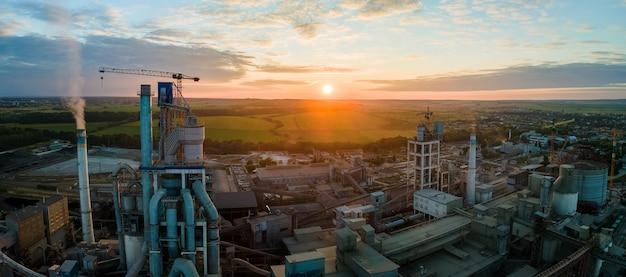 Vue aérienne de l'usine de ciment avec une structure de centrale en béton élevée et une grue à tour dans la zone de production industrielle. concept de fabrication et d'industrie mondiale.