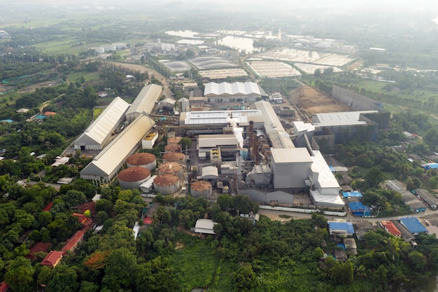 Vue aérienne, usine de transformation de mélasse et de sucre avec émission de fumée des cheminées à la campagne