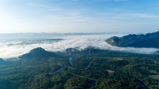 Vue aérienne des vagues de brouillard qui coule sur la forêt tropicale humide de montagne