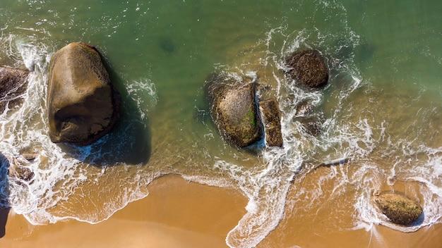 Vue aérienne de vagues douces frappant les rochers sur une côte de sable de plage brésilienne. balnéaire camboriu.