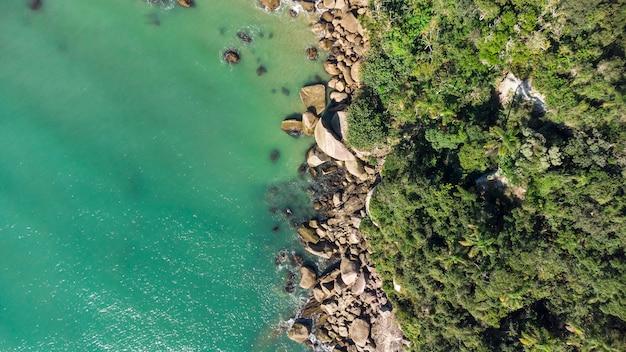 Vue aérienne des vagues frappant les rochers sur une plage brésilienne. balnéaire camboriu.