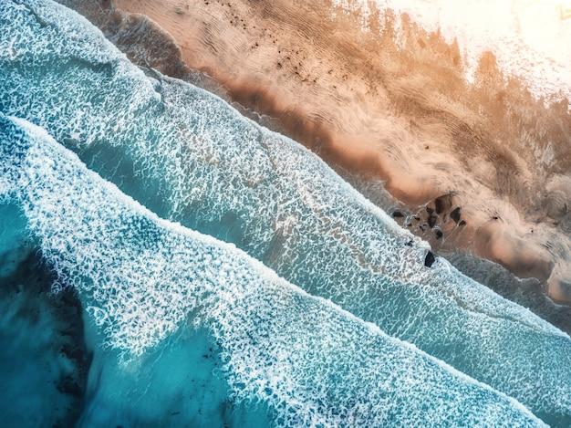 Vue aérienne des vagues, des rochers et de la mer transparente