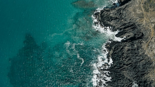 Vue aérienne de vagues s'écraser sur une côte de lave hawaïenne