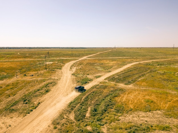 Vue aérienne de véhicule hors route 4x4 camion se déplaçant sur un champ poussiéreux d