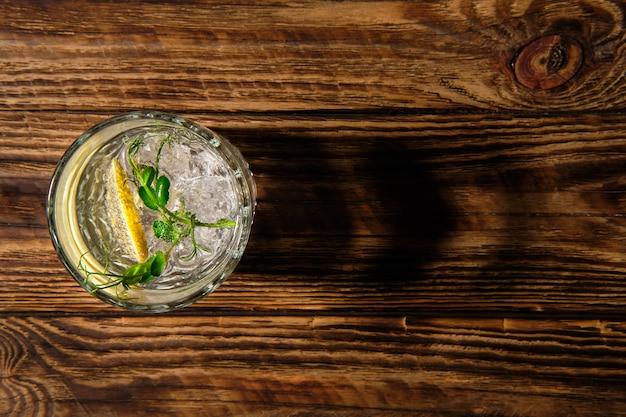 Vue aérienne de verre avec de l'eau froide avec de la glace et du citron jetant une ombre sur une table en bois