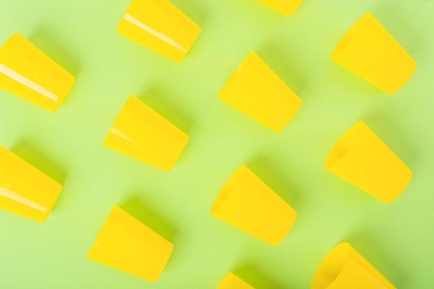 Vue aérienne de verres en plastique jaunes sur fond vert