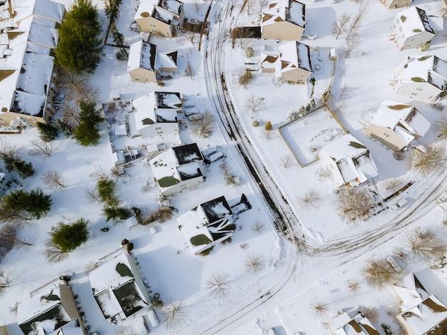 Vue aérienne vers le bas sur les maisons couvertes et les routes dans les cours d'hiver couvertes de neige avec de la neige