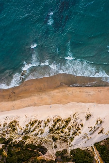 Vue aérienne verticale d'une plage avec une mer bleue