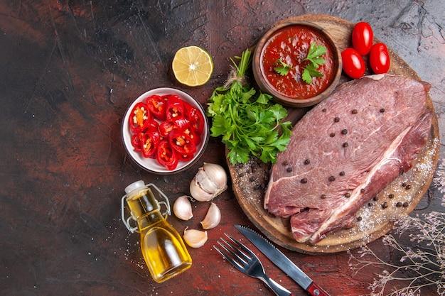 Vue aérienne de la viande rouge sur un plateau en bois et du ketchup vert à l'ail et une bouteille d'huile tombée au poivre haché sur fond sombre