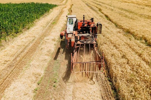 Vue aérienne d'une vieille moissonneuse-batteuse se met en route pour récolter le blé moissonneuse récolte le blé dans le ...