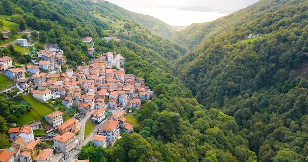 Vue aérienne sur le village italien de montagne, garzeno. portrait de maisons aux toits rouges parmi les arbres au sommet de la montagne en été.
