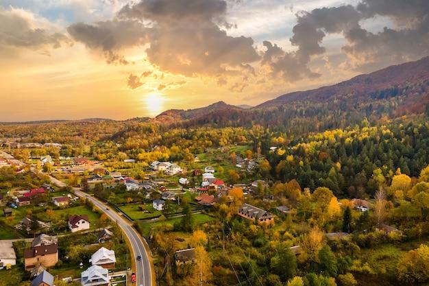 Vue aérienne d'un village rural avec de petites maisons entre les collines de montagne d'automne couvertes de pins jaunes et verts au coucher du soleil.