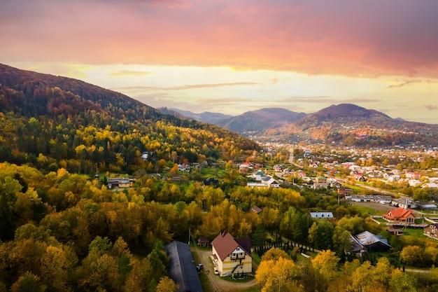 Vue aérienne d'un village rural avec de petites maisons entre les collines de montagne d'automne couvertes de pins jaunes et verts.