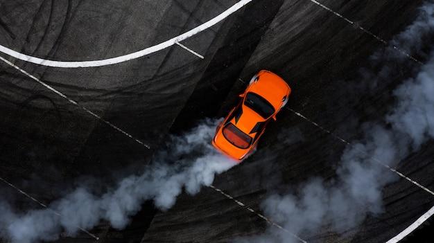 Vue aérienne de la voiture à la dérive sur la piste de course en asphalte avec beaucoup de fumée.