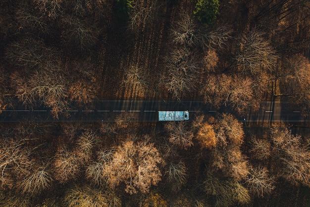 Vue aérienne d'une voiture roulant sur la route goudronnée entourée d'arbres dorés en automne