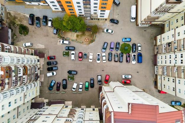 Vue aérienne des voitures garées sur le parking entre les immeubles d'habitation élevés.