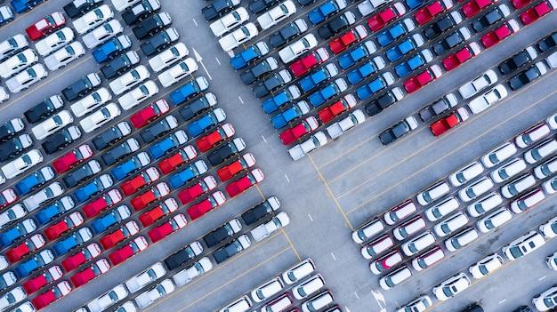 Vue aérienne de voitures neuves à vendre ligne de lot de stock, inventaire de concessionnaire de voitures neuves import export logistique logistique d'entreprise.