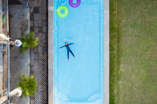 Vue aérienne ou vue de dessus de l'enfant nage dans la piscine