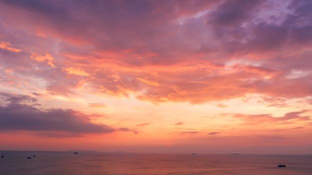 Vue aérienne de la vue sur le paysage marin et petit porte-conteneurs naviguant en mer sur fond de ciel rose du soir