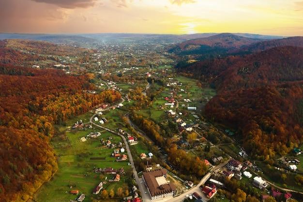 Vue aérienne d'une zone rurale du village avec de petites maisons entre les collines de montagne d'automne couvertes de forêt d'épinettes jaunes et vertes.