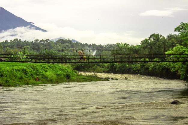 Vue d'un agriculteur marchant sur un pont suspendu sur une rivière rapide dans le nord de bengkulu, indonésie
