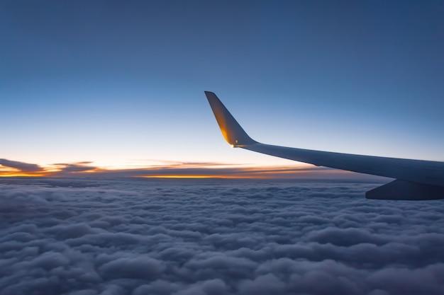 Vue d'aile d'avion depuis l'avion avec ciel nuageux après le coucher du soleil.