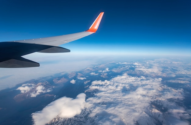 Vue de l'aile de l'avion, nuages et ciel vus à travers la fenêtre de l'avion