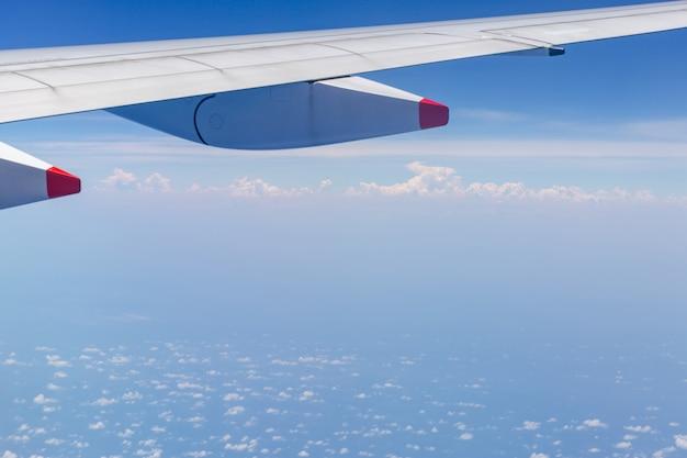 Vue d'aile d'avion par la fenêtre le fond de ciel nuageux, concept de vacances voyage et vacances
