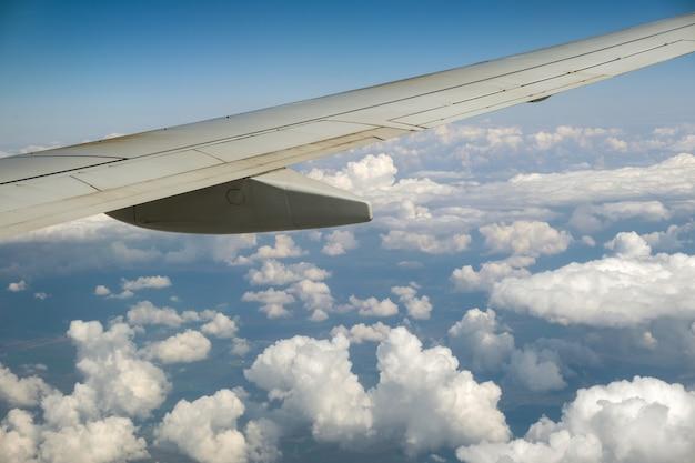 Vue de l'aile d'avion à réaction de l'intérieur survolant des nuages gonflés blancs dans le ciel bleu. concept de voyage et de transport aérien.