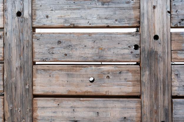 Vue de l'ancienne clôture faite de planches de bois massives disposées horizontalement avec des trous ronds disposés au hasard. concept de texture, intérieur