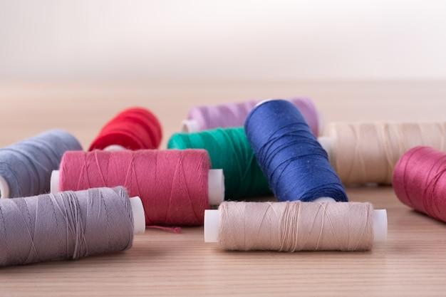 Vue d'angle de bobines de fil de coton colorés dispersés sur table en bois