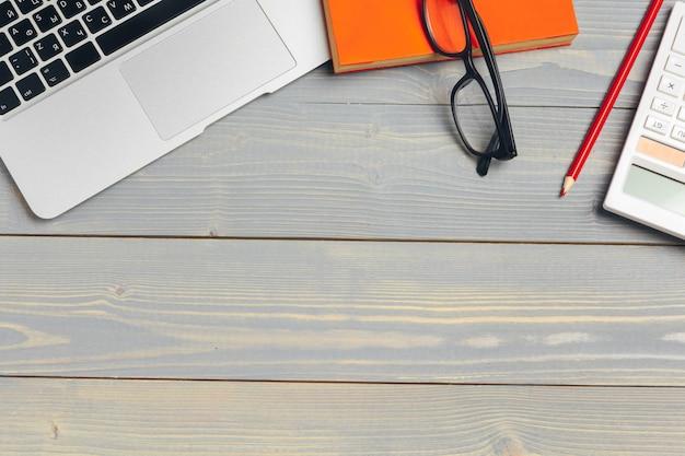 Vue en angle du clavier d'ordinateur portable et des lunettes avec diverses fournitures de bureau sur un bureau en bois