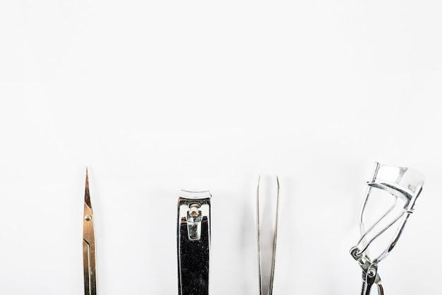 Vue en angle élevé des ciseaux; coupe-ongles; pincette et recourbe-cils sur fond blanc