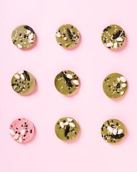 Vue d'angle élevé de dessert rond rose parmi les desserts verts disposés en rangée sur fond