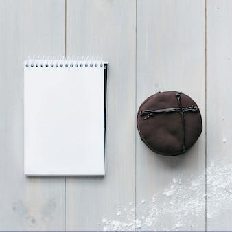 Vue d'angle élevé de macaron au chocolat et bloc-notes vide sur une planche en bois