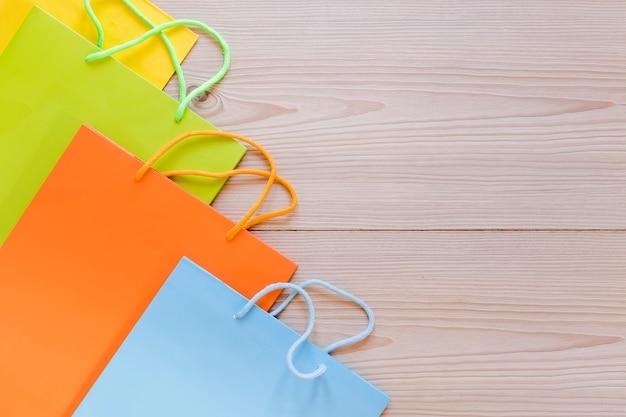 Vue d'angle élevé de sacs à provisions multicolores sur fond en bois