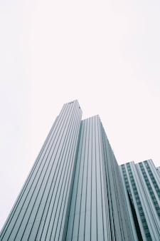 Vue d'angle faible d'un gratte-ciel moderne avec des fenêtres bleues et blanches sous un ciel blanc
