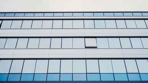 Vue d'angle de perspective et de dessous à l'arrière-plan texturé du bâtiment en verre contemporain