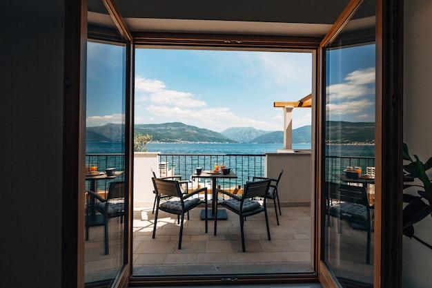 Vue de l'appartement sur mer balcon avec salon de jardin et petit déjeuner sur la table croissants