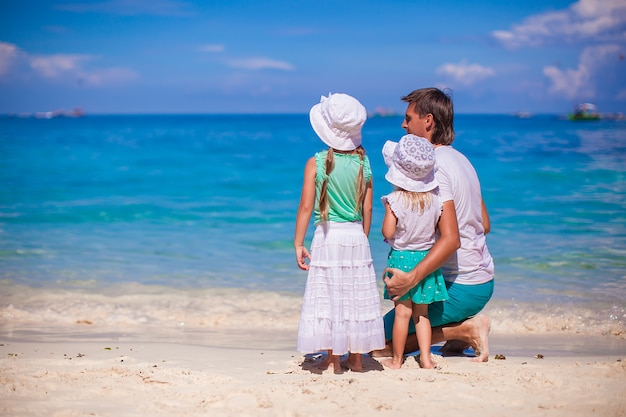 Vue arrière d'adorables petites filles et jeune père sur une plage blanche tropicale