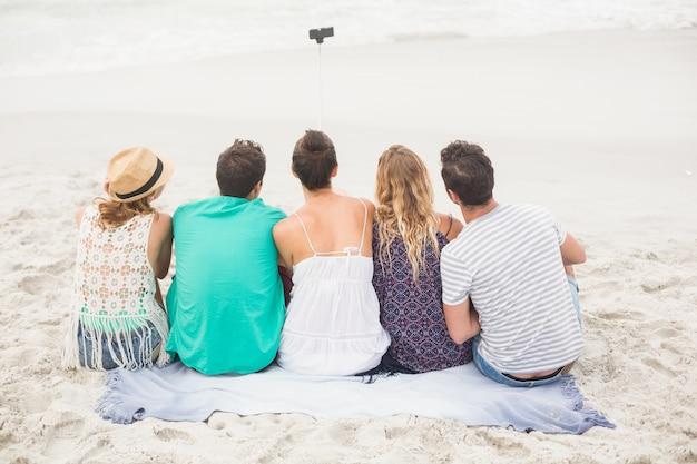 Vue arrière d'un ami prenant un selfie sur la plage