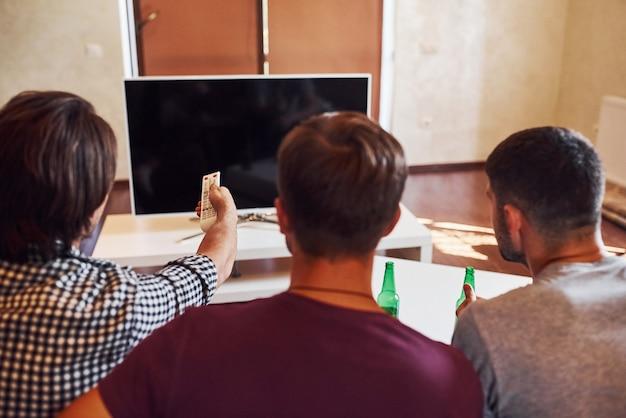 Vue arrière d'amis regardant la télévision et tenant la télécommande en main.