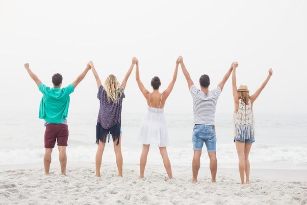 Vue arrière d'amis se tenant la main et debout dans une rangée