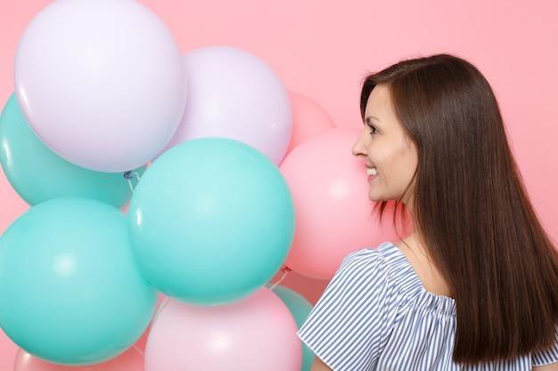 Vue arrière arrière de la belle jeune femme heureuse tendre en robe bleue tenir des ballons à air colorés regardant de côté isolés sur fond rose vif. fête d'anniversaire, concept d'émotions sincères.