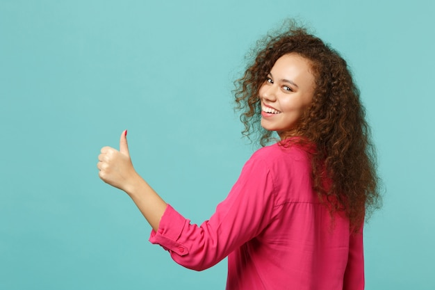 Vue arrière arrière d'une fille africaine souriante dans des vêtements décontractés regardant en arrière, montrant le pouce vers le haut isolé sur fond bleu turquoise en studio. concept de mode de vie des émotions sincères des gens. maquette de l'espace de copie.