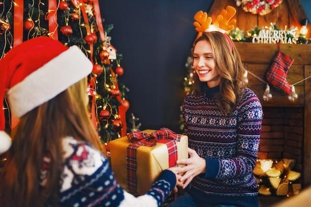 Vue arrière de l'arrière d'une maman joyeuse et sa fille fille mignonne échangeant des cadeaux.