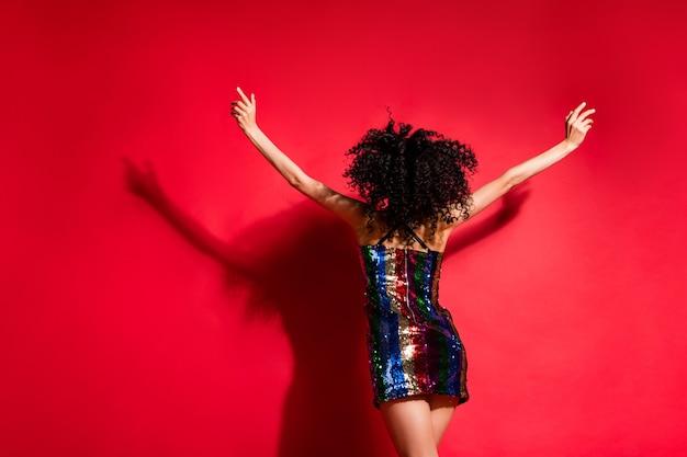 Vue arrière arrière de sa superbe fille mince aux cheveux ondulés s'amusant à danser disco reste isolée sur fond de couleur rouge vif