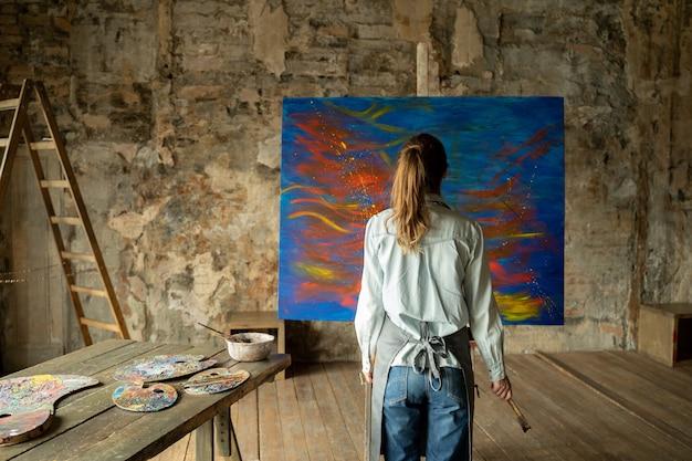 Vue arrière de l'artiste féminine s'approche d'un chevalet avec une peinture