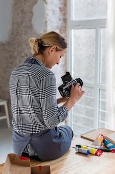 Vue arrière de l'artiste en tablier tenant l'appareil photo
